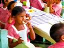 Nursery school children enjoy a snack of peanut butter on cassava bread in Aranaputa, Guyana.